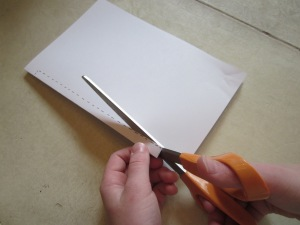 Step 3: Pick up the second pile of papers. Starting about 1-inch from the edge of the paper, cut a long skinny rectangle out of the center of the page. Stop 1-inch before the other end of the paper. This is the same as cutting a Valentine heart out of the center of a piece of paper.
