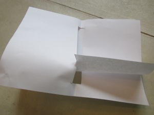 Step 5: Shaking a little, unroll the hot dog papers until they fit into the notch at the bottom and top of the pages.
