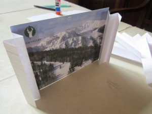 """Step 1: Put a little glue along the inside edge of two of your hinges and place them on the left and right sides of the back of your post card. Repeat this step for each 4"""" x 6"""" card."""