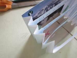 Step 5: Assem­ble your tun­nel book, work­ing from the back (line 3 of your haiku) to the front, glu­ing the back of each hinged page to the hinges behind it.