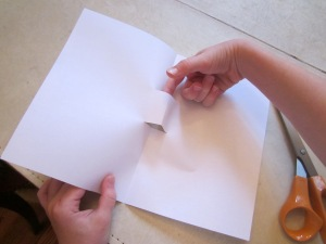 Step 2: Open paper and poke finger into the cut section in the center of the paper and gently pull forward to make a stair step.