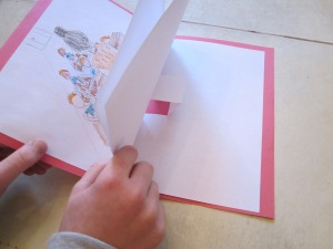 Step 5: When one page is completed, use a new piece of paper and create a new pop-up page. Do you second page of illustrations and text. When pages are ready, you will attach the back of the bottom of the first page to the back of the top of the second page. Use a glue stick and run glue around the outside edges only. If you glue to close to the center, it might stick down the pop ups.