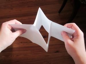 Step 5: Hold each side with one hand and push towards the center until your fingers meet. The center of the paper will push out creating 4 flaps.