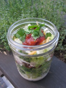 layered mexican salad in a jar top view